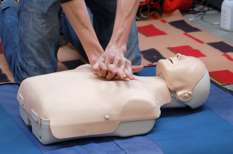 Man practising CPR on dummy