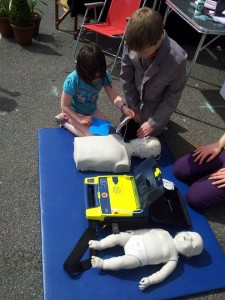 Boy teaching girl how to use a public access defibrillator
